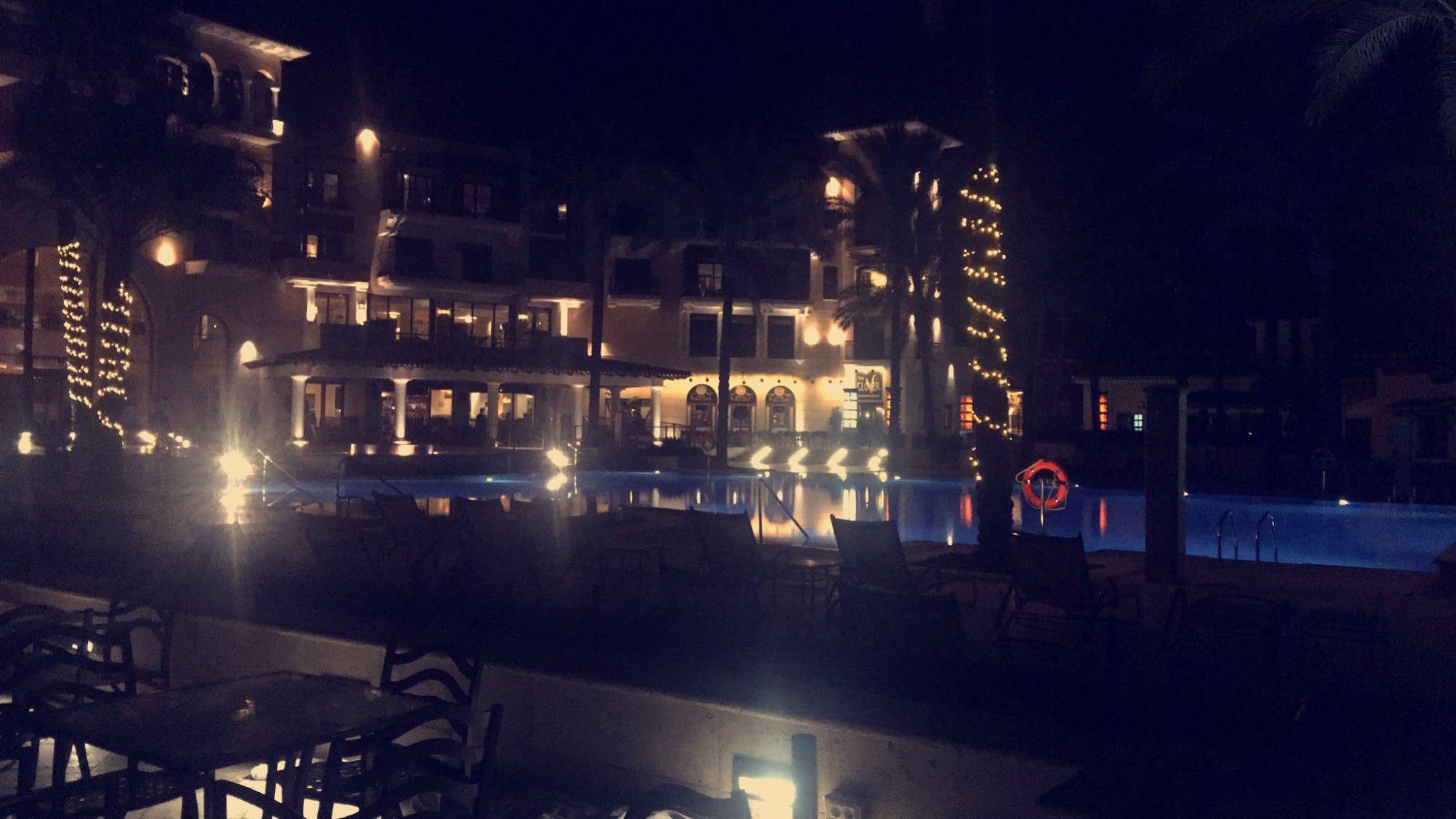 Baksidan på Mar Menors hotell med fin ute belysning och pool.